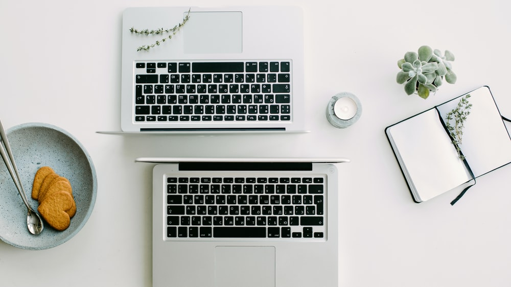 two silver laptop computers besides clear glass jar