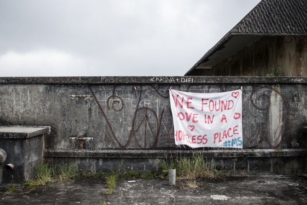 vandalized wall with hanging banner