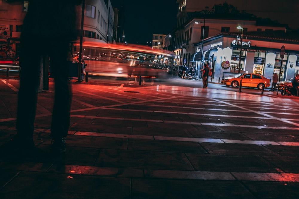 man standing near pedestrian lane at night