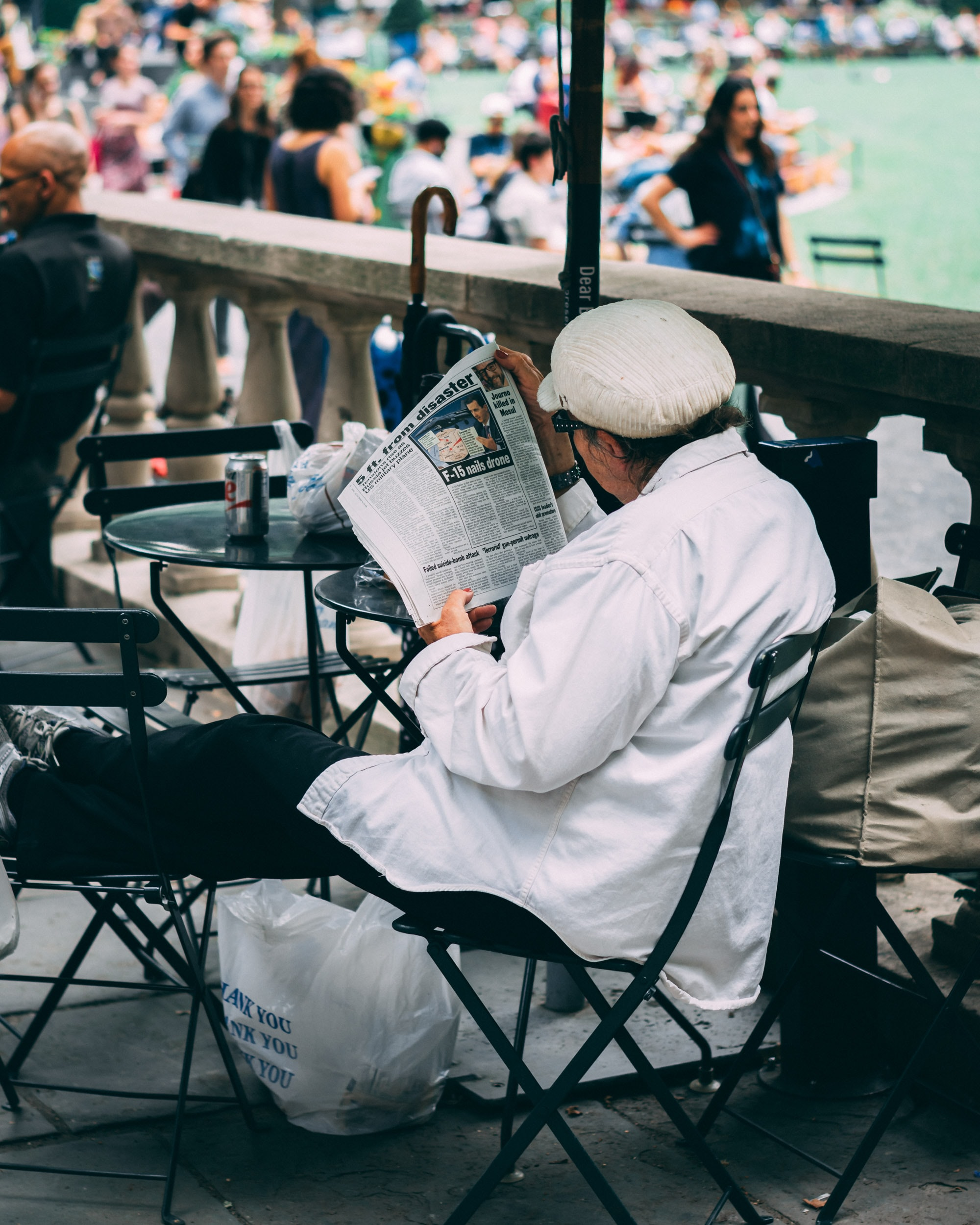 woman sitting on chair while reading a newspaper near body of water
