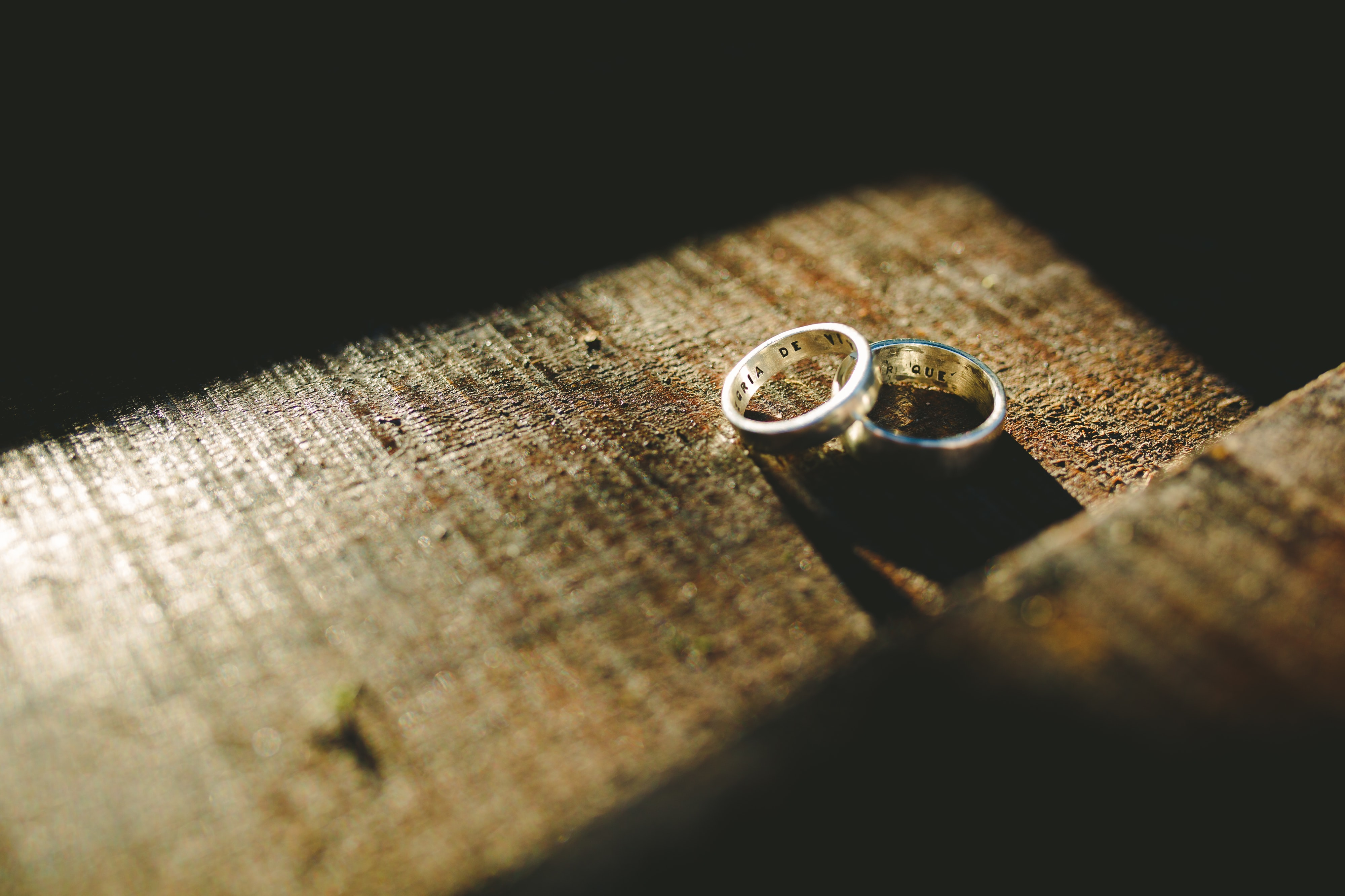 two silver-colored engagement rings on top brown surface