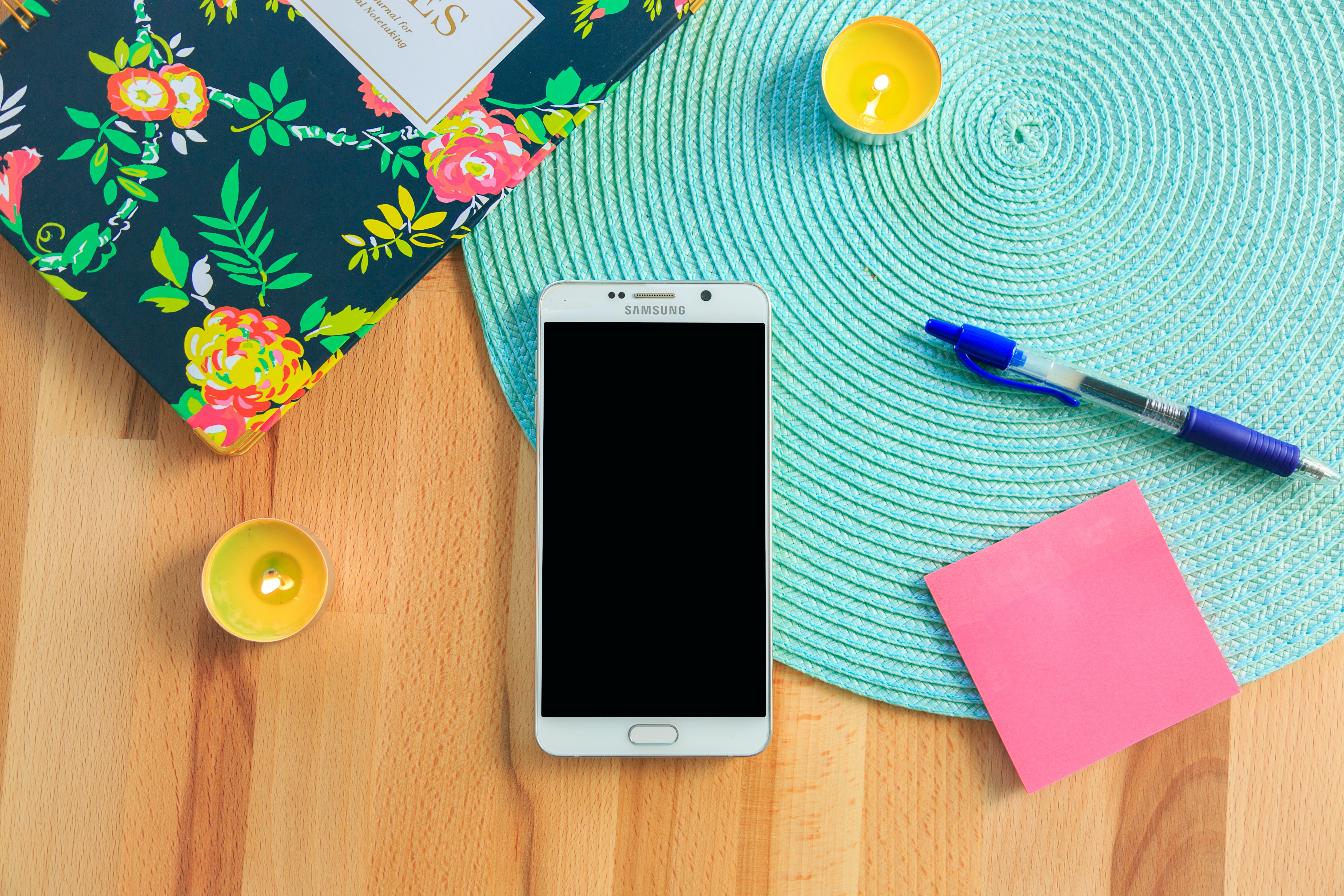 white Samsung Galaxy smartphone on top of blue place mat near blue click pen