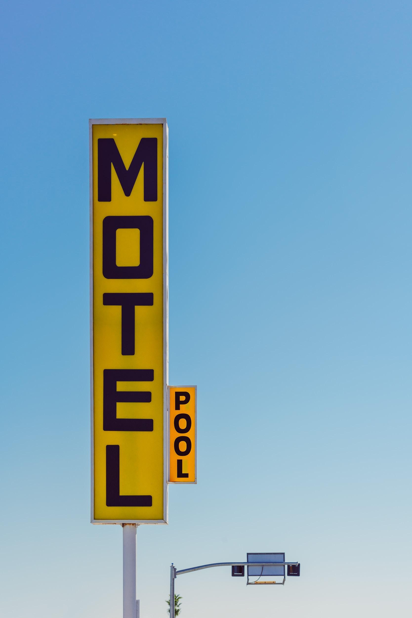 yellow and black Motel signage taken at daytime