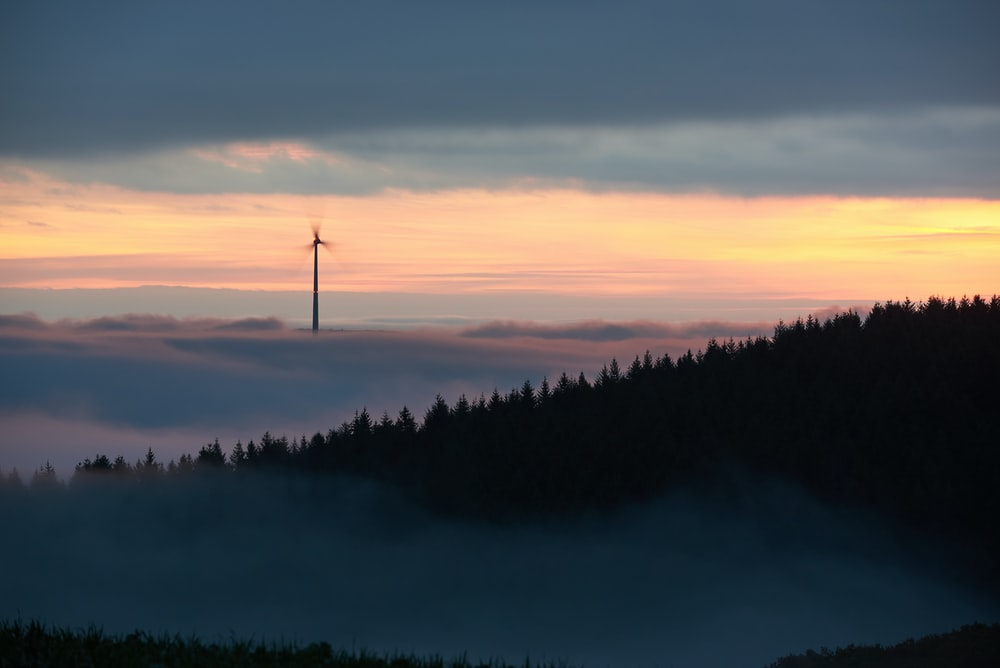 wind turbine surrounded by fog during dawn