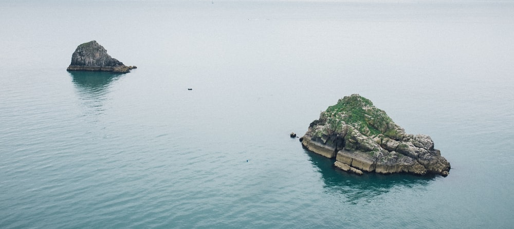 rock formation on body of water scenery