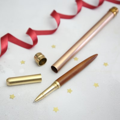 brass-colored pen with case beside red ribbon on white surface