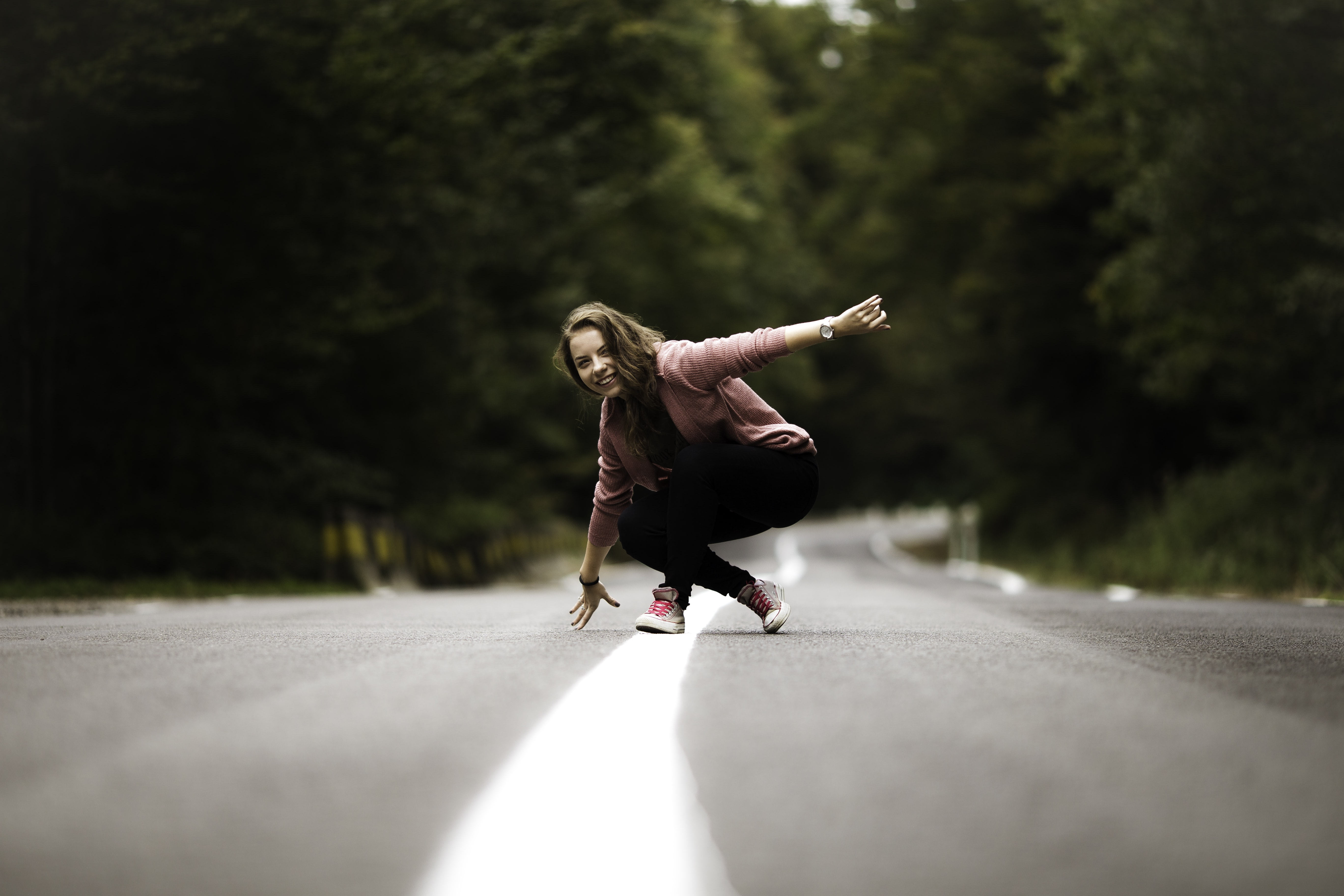 woman sitting on middle of the road