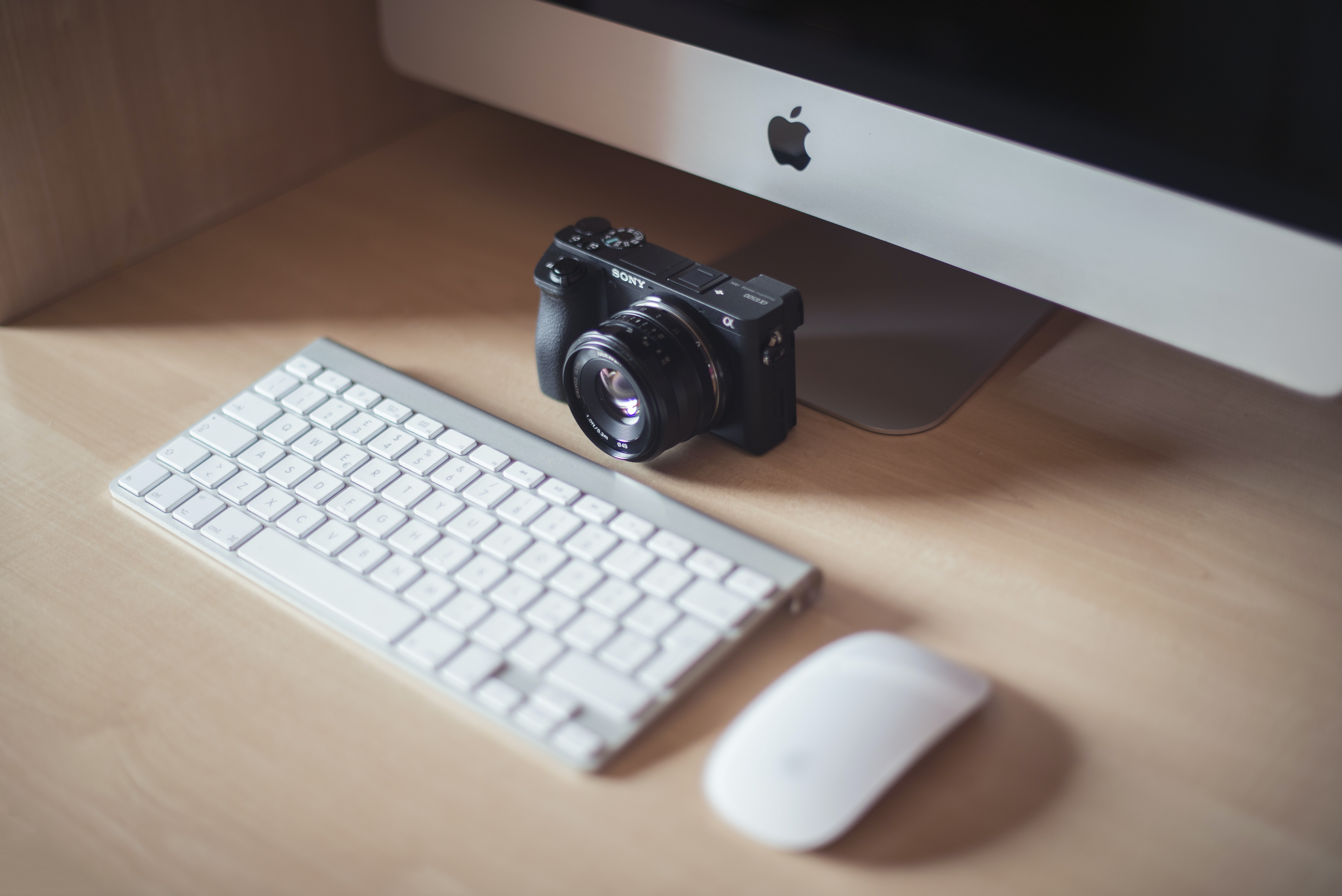 DLSR beside Apple magic keyboard and mouse