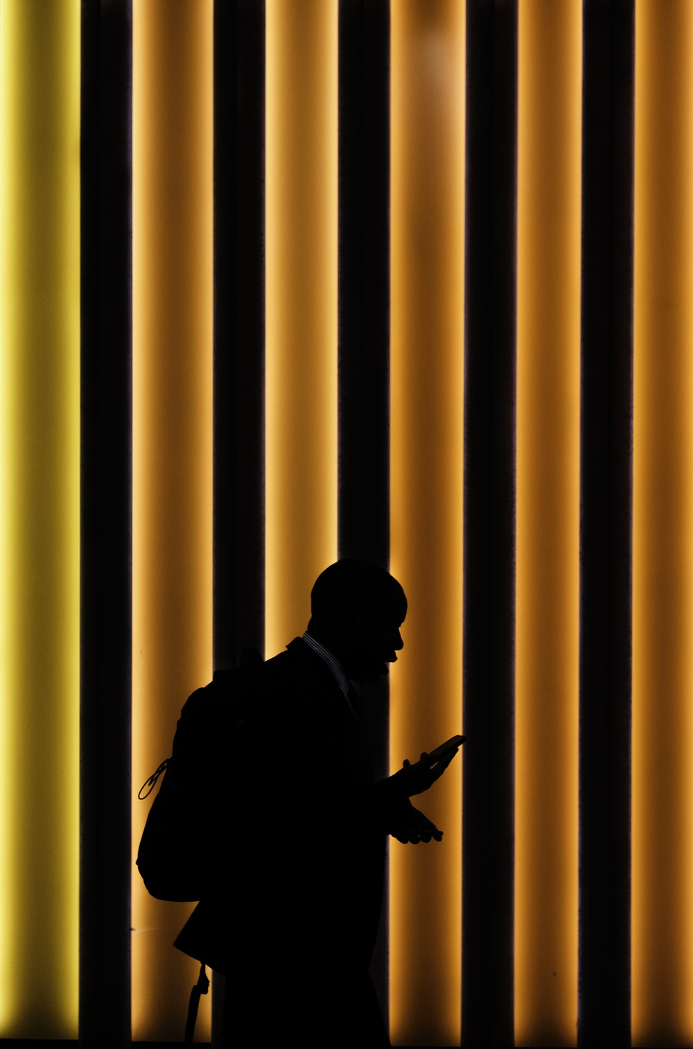 silhouette of man standing on orange and black striped background