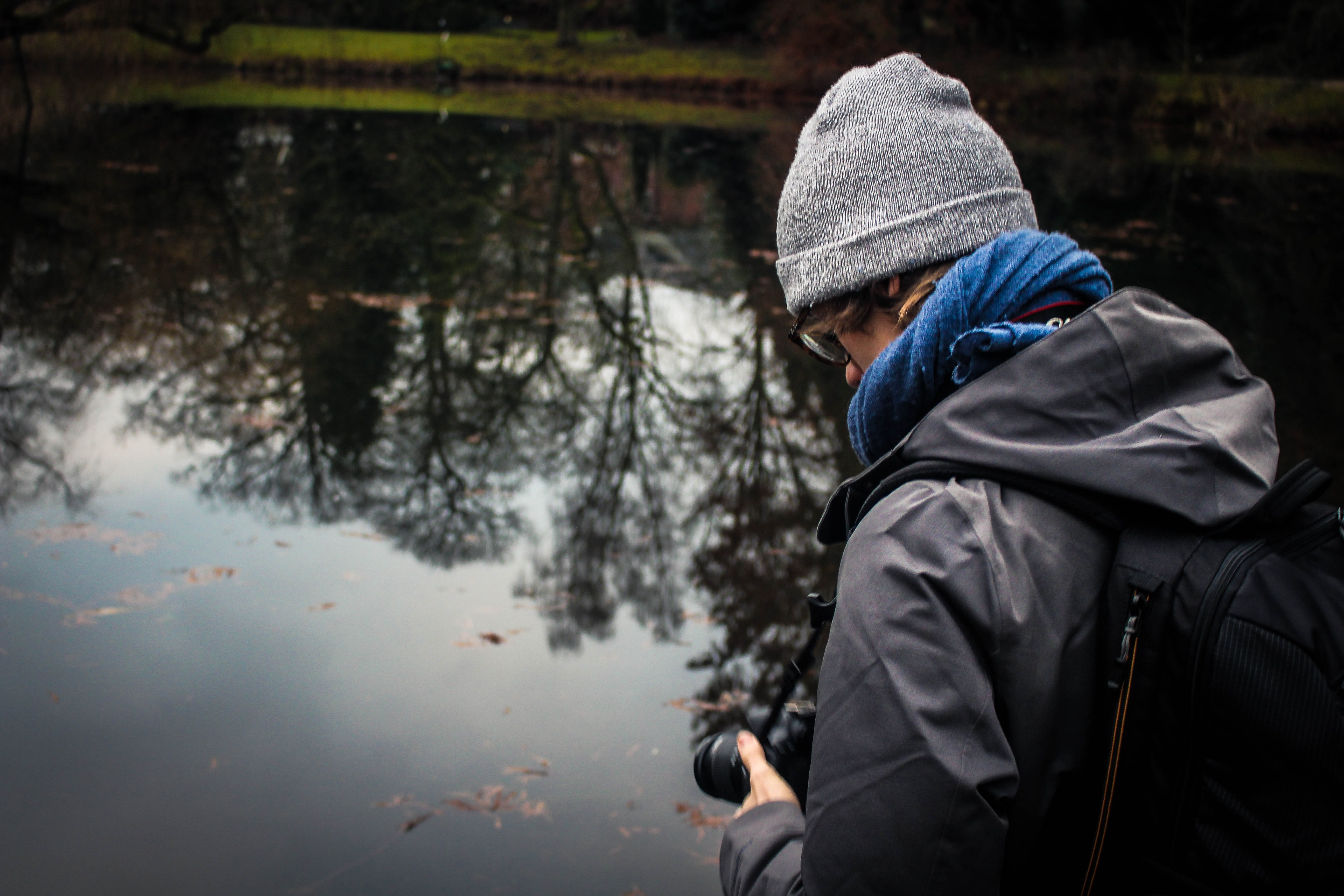 man holding camera infront of water
