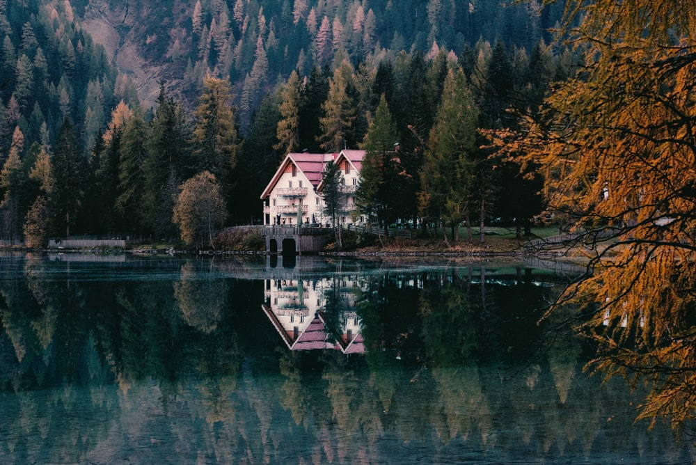 landscape photo of white and red house near lake