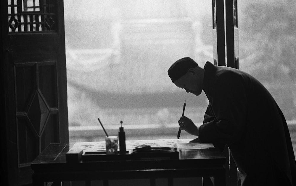 man in black suit holding pen