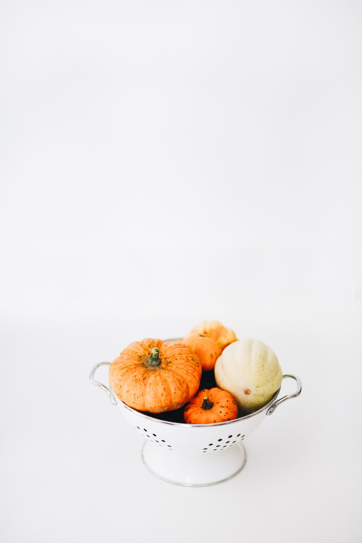 four round orange squashes on colander