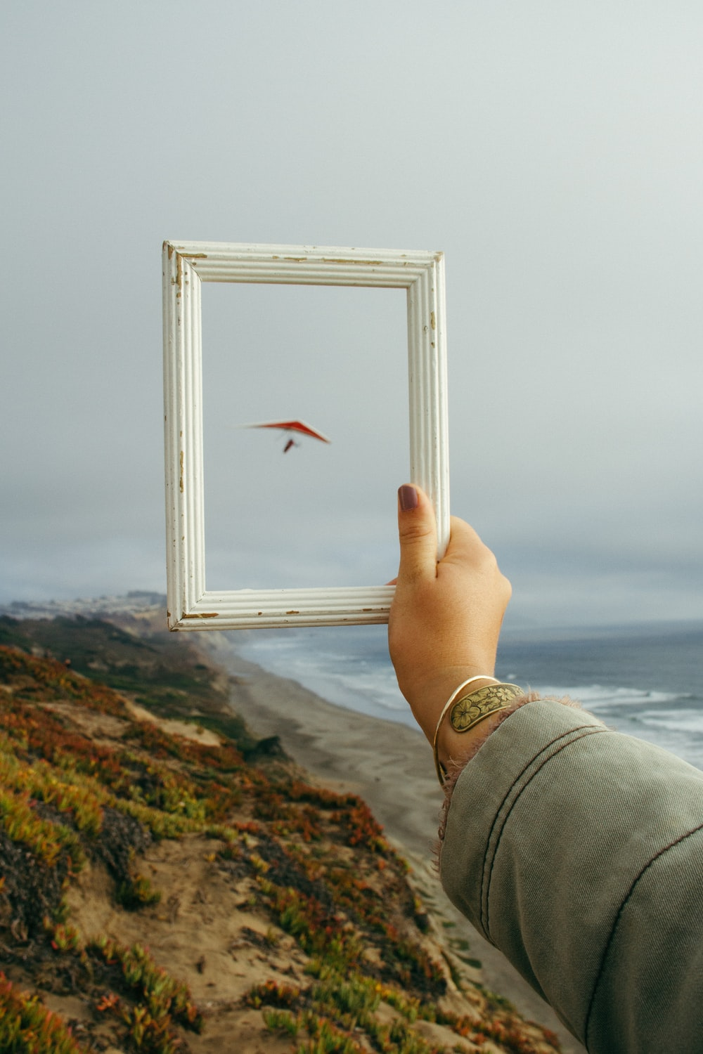 person holding rectangular white photo frame standing on rock formation near body of water