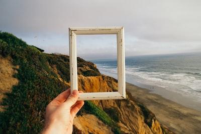 白いフレームを左手で持ってフレーム越しに海を見ている様子