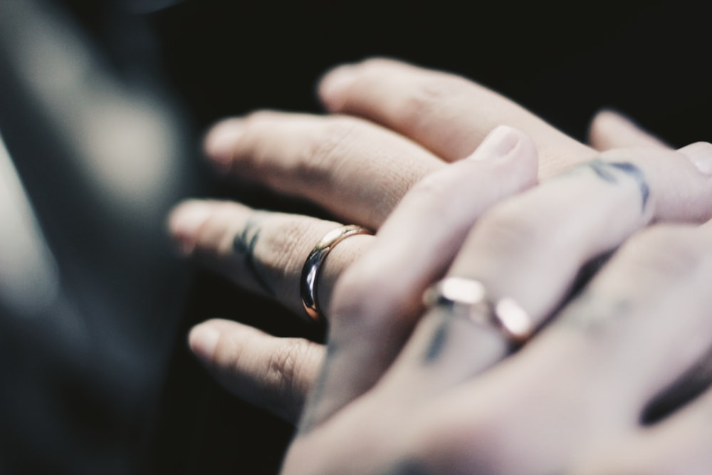 person showing two gold-colored rings