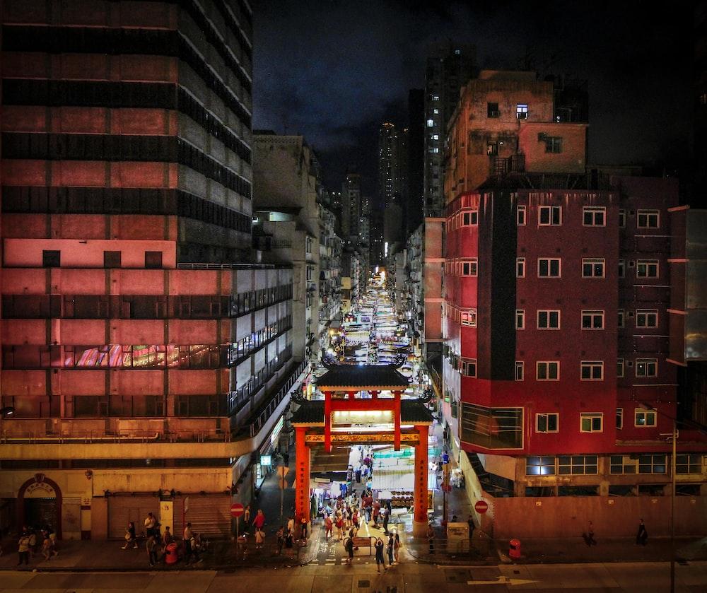 people walking between buildings at night