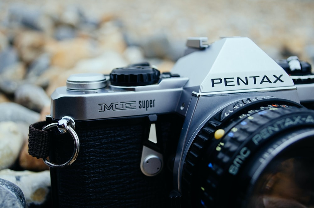 black and silver Pentax SLR camera