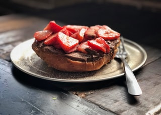 selective focus photography of plate of bread with slice of strawberries