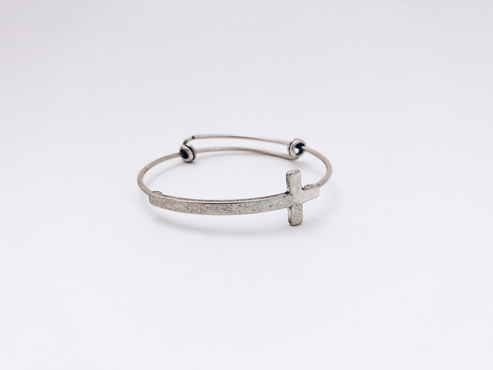 closeup photo of silver-colored cross bangle