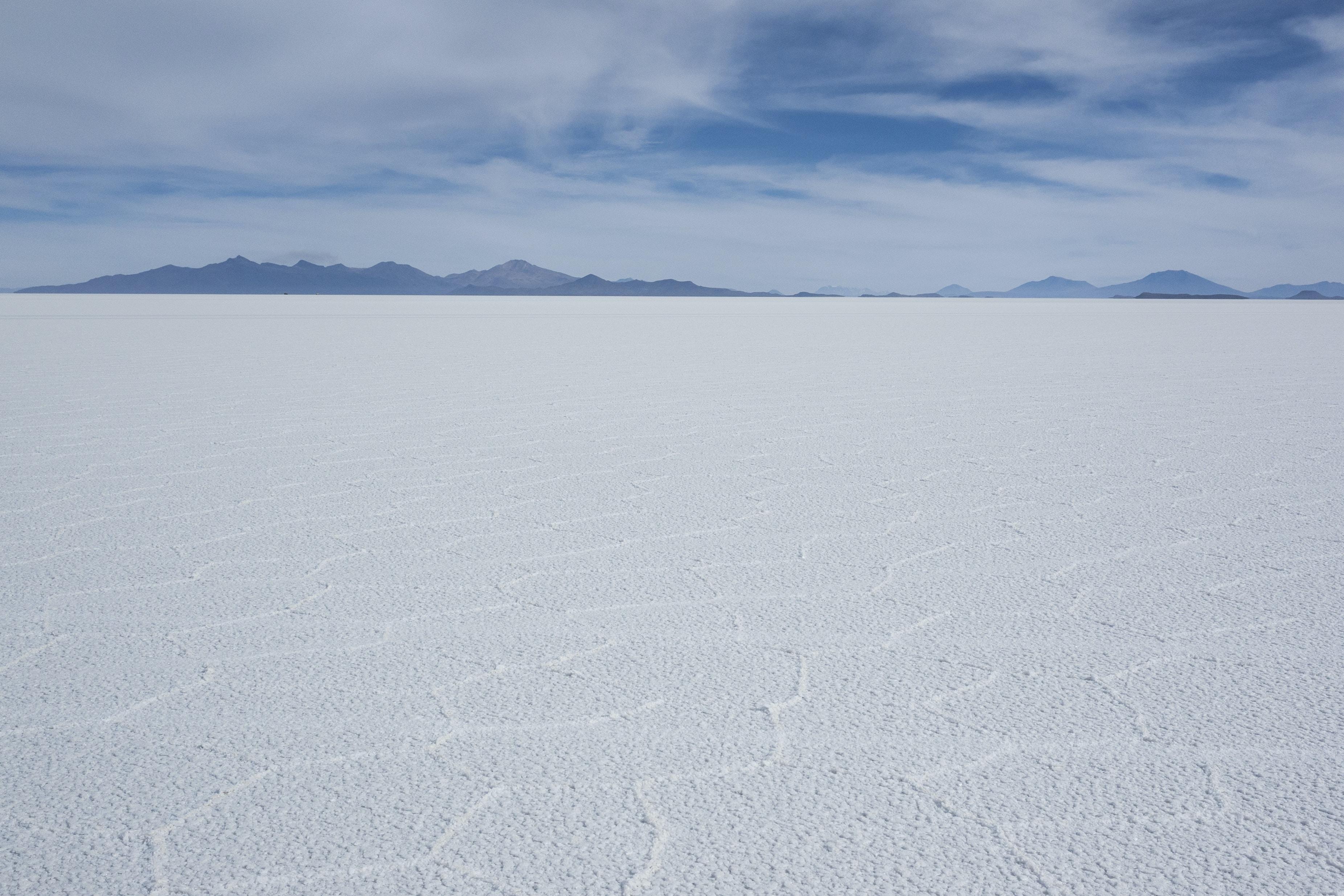 white snow field under white clouds at daytime
