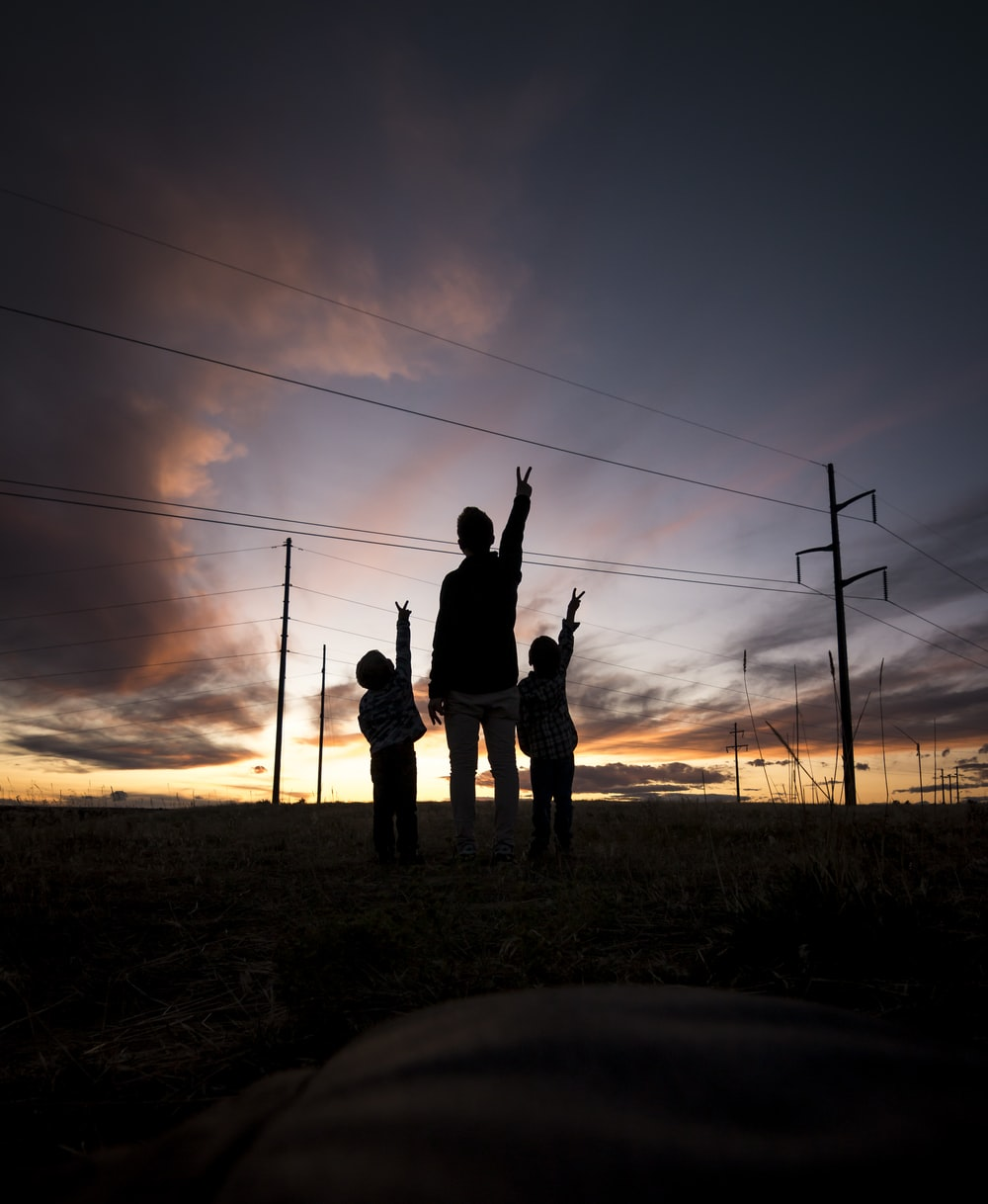 silhouette of three person during daytime