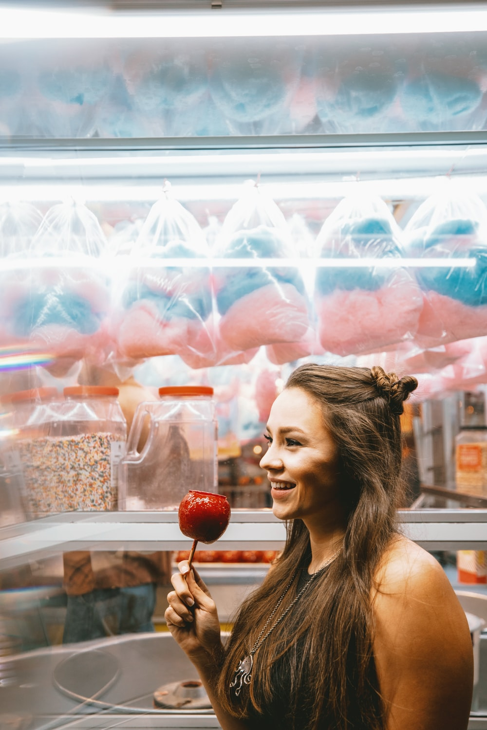woman holding red apple while smiling