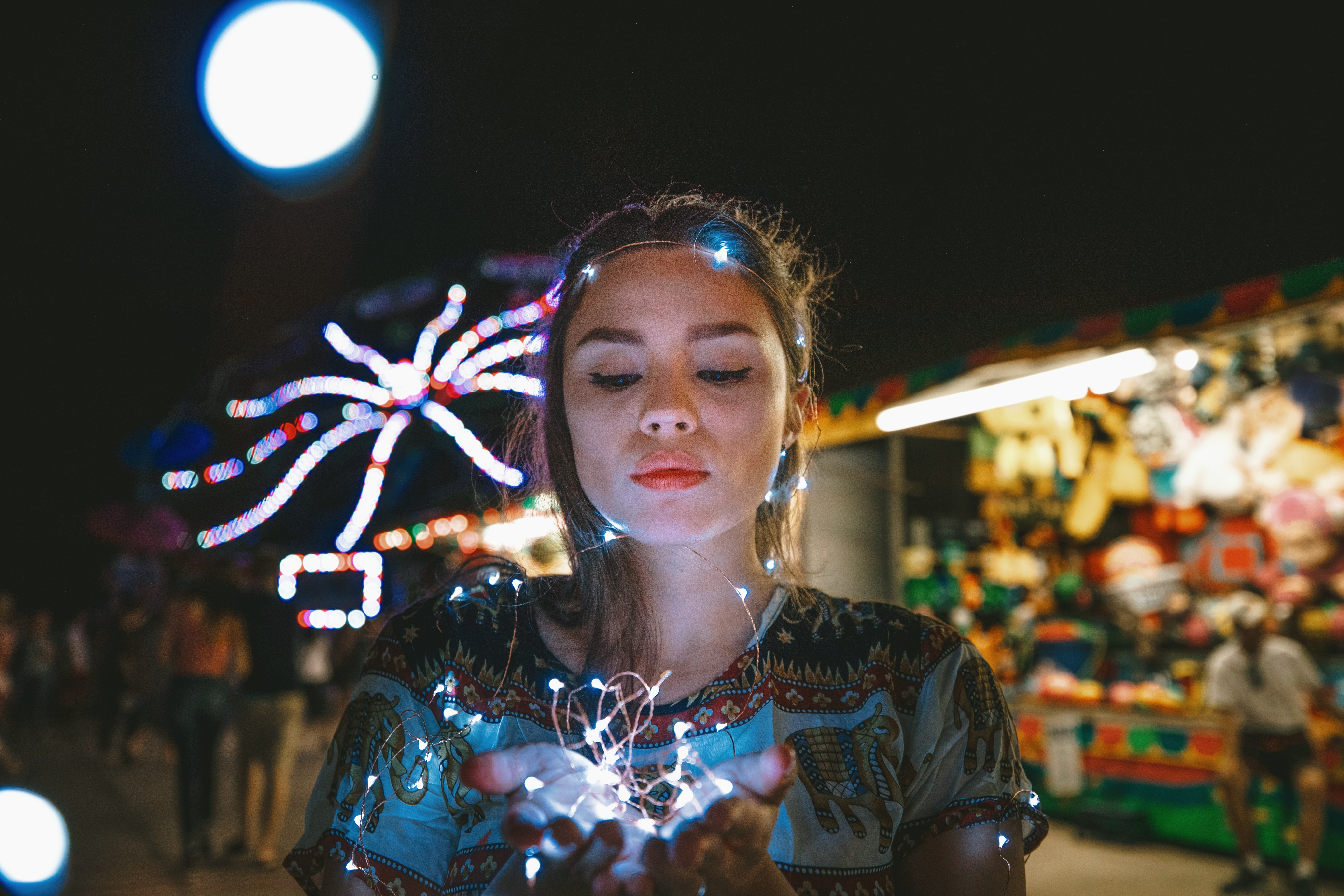 woman wearing multicolored shirt holding lighted string lights
