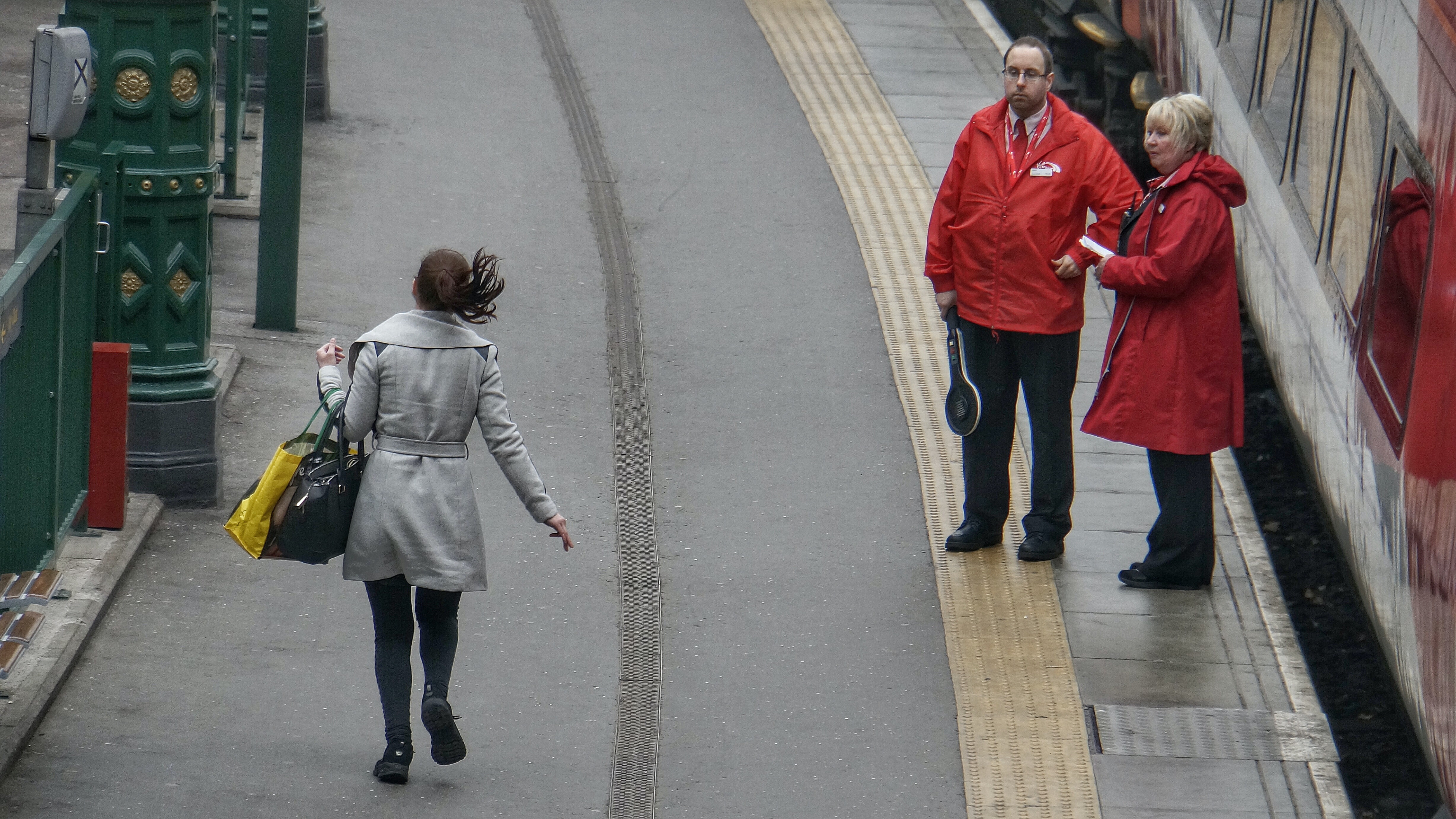 woman in gray coat walking on the road during day time