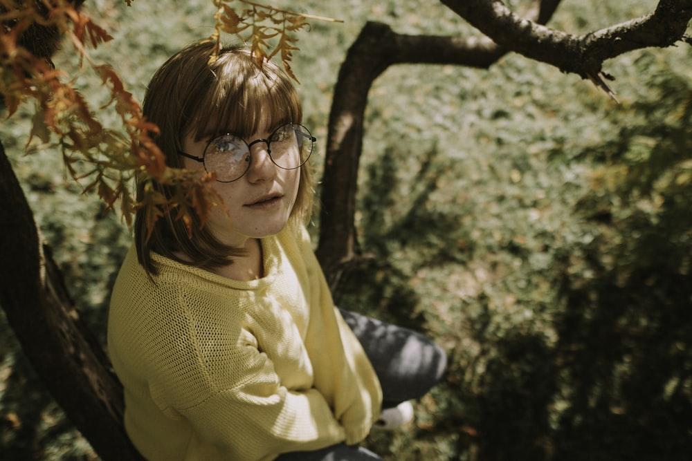 girl sitting on tree during daytime