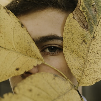 brown leaves on person face during daytime