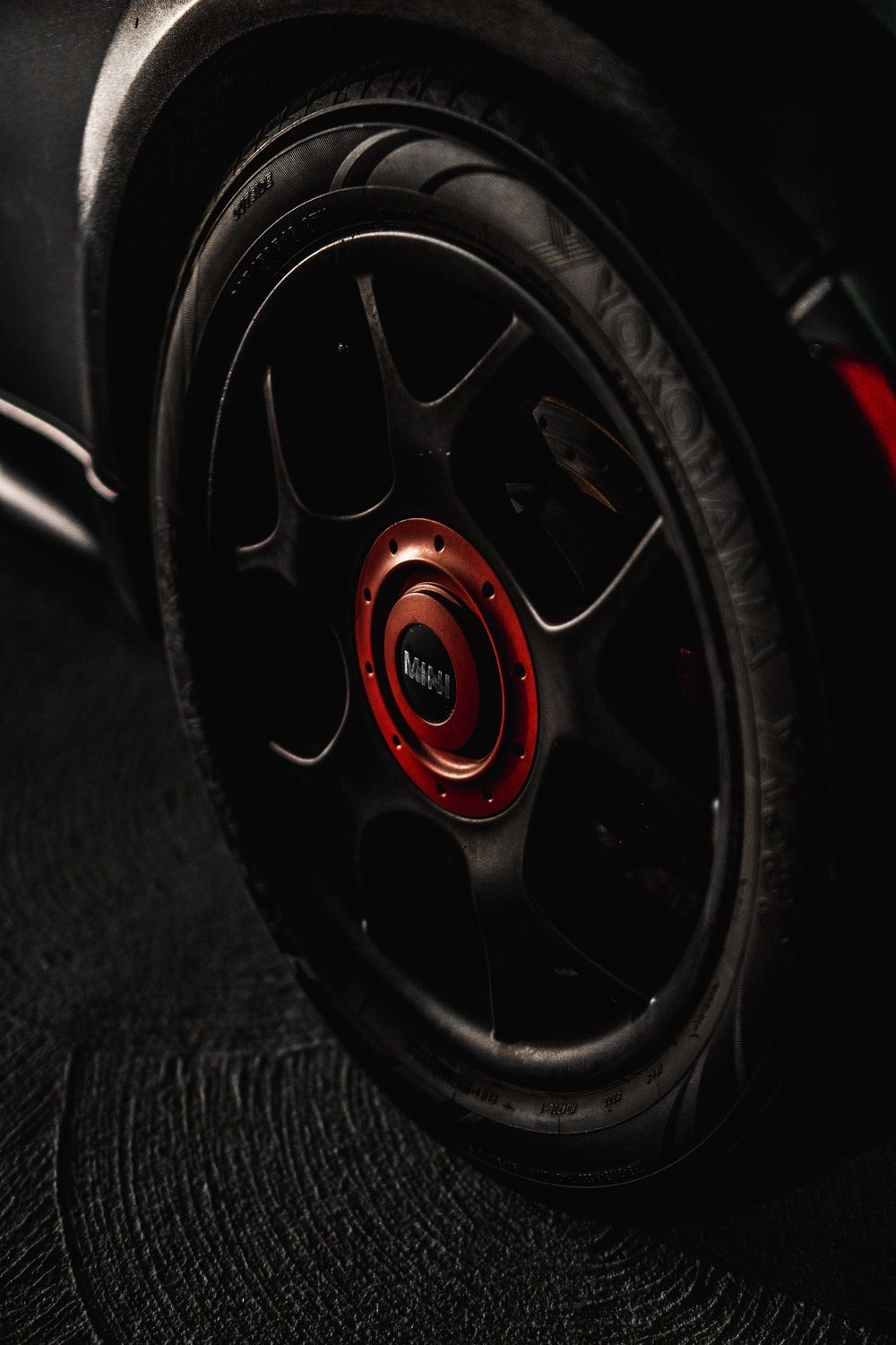 black and red multi-spoke car wheel with tire