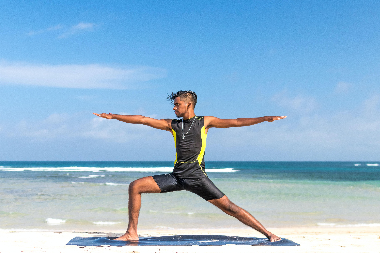 man standing at seashore while yoga
