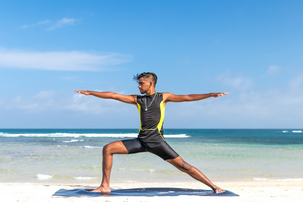 man standing at seashore while yoga
