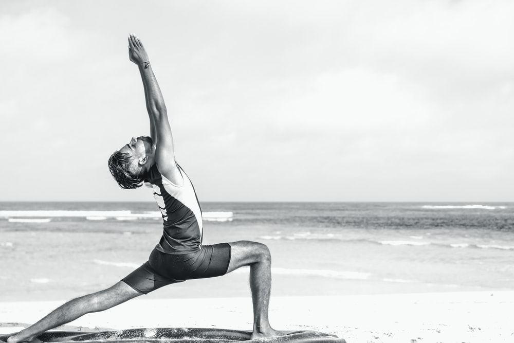 man stretching on seashore