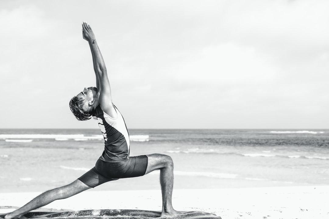 Asian yoga man practice yoga on the beach with a clear blue sky background. Yogi on the tropical beach of Bali island, Indonesia.