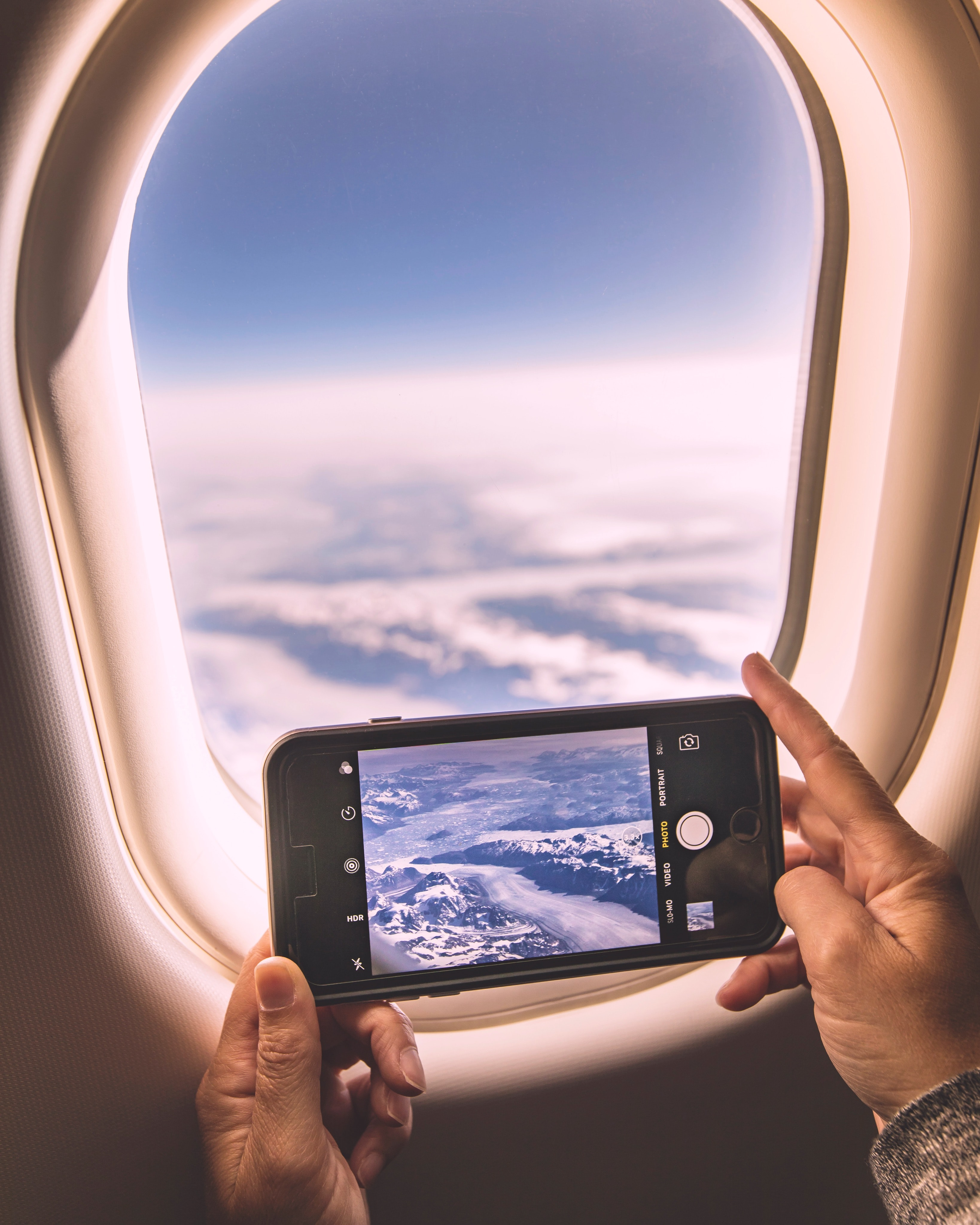 selective focus photography of person holding iPhone while taking photo of sky