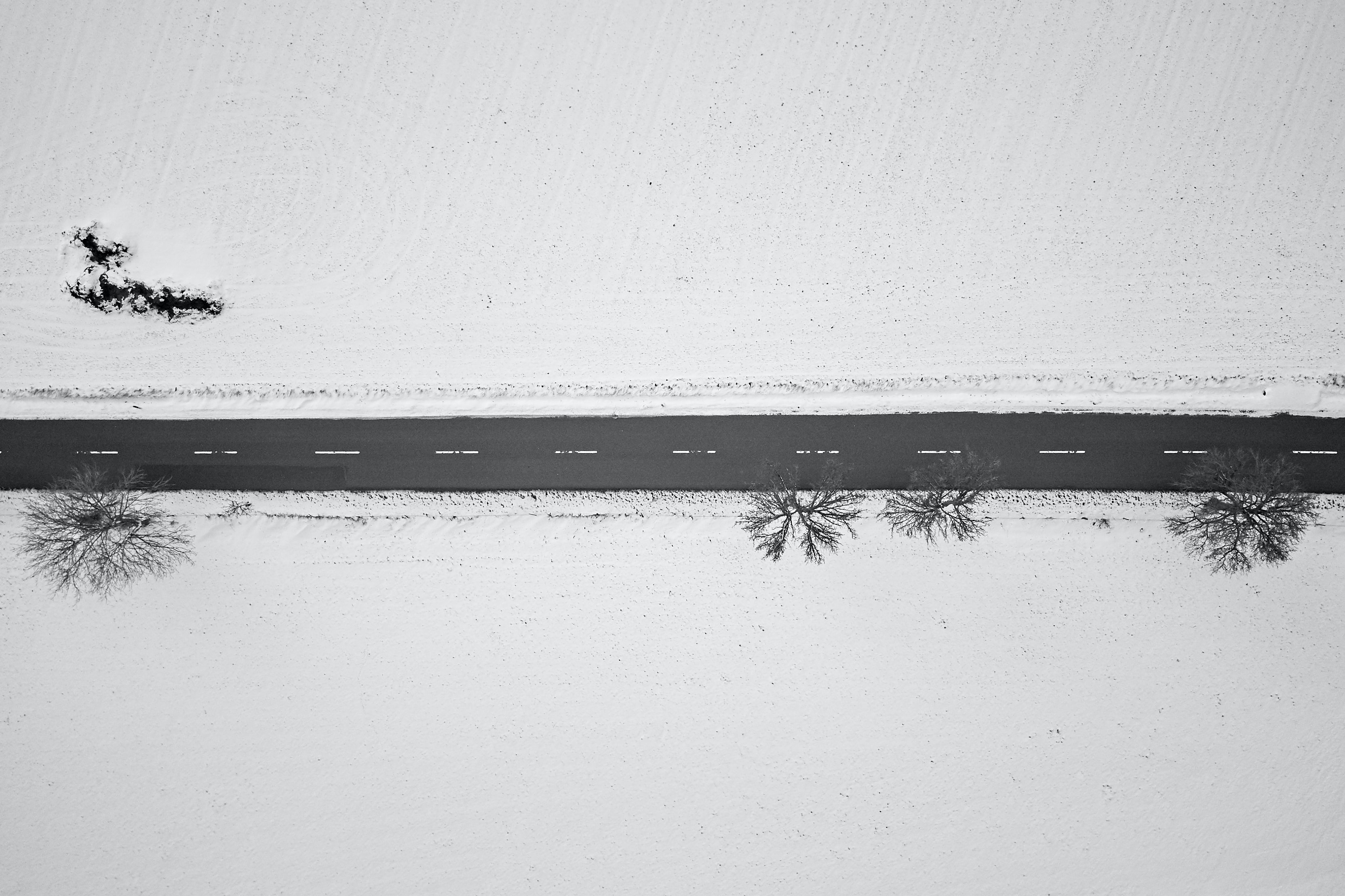 bird's eye view of road in the middle of snow field