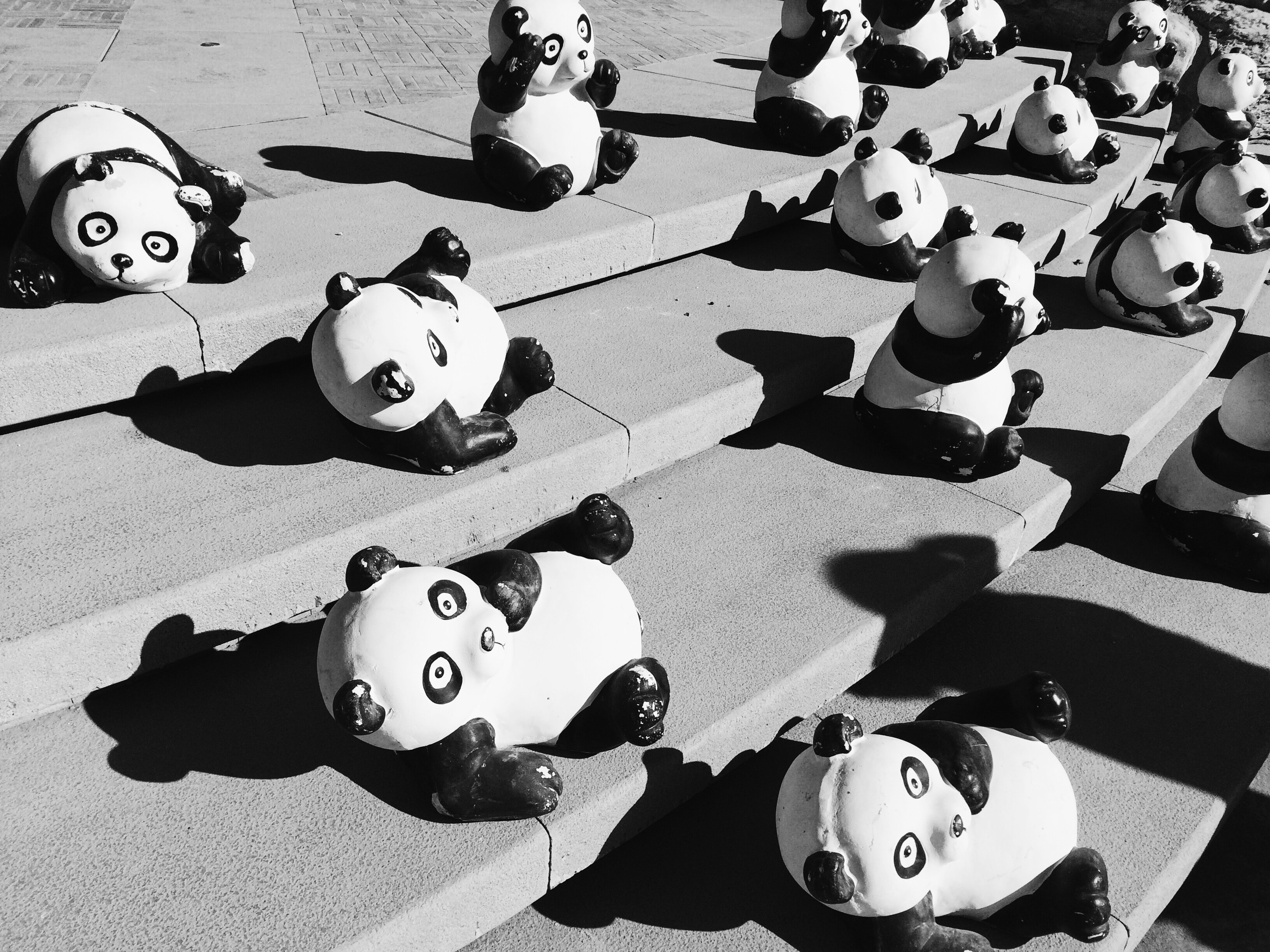 Panda statues on gray concrete stairs during daytime