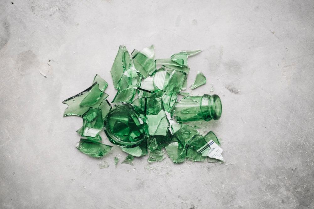 broken green glass bottle on the ground