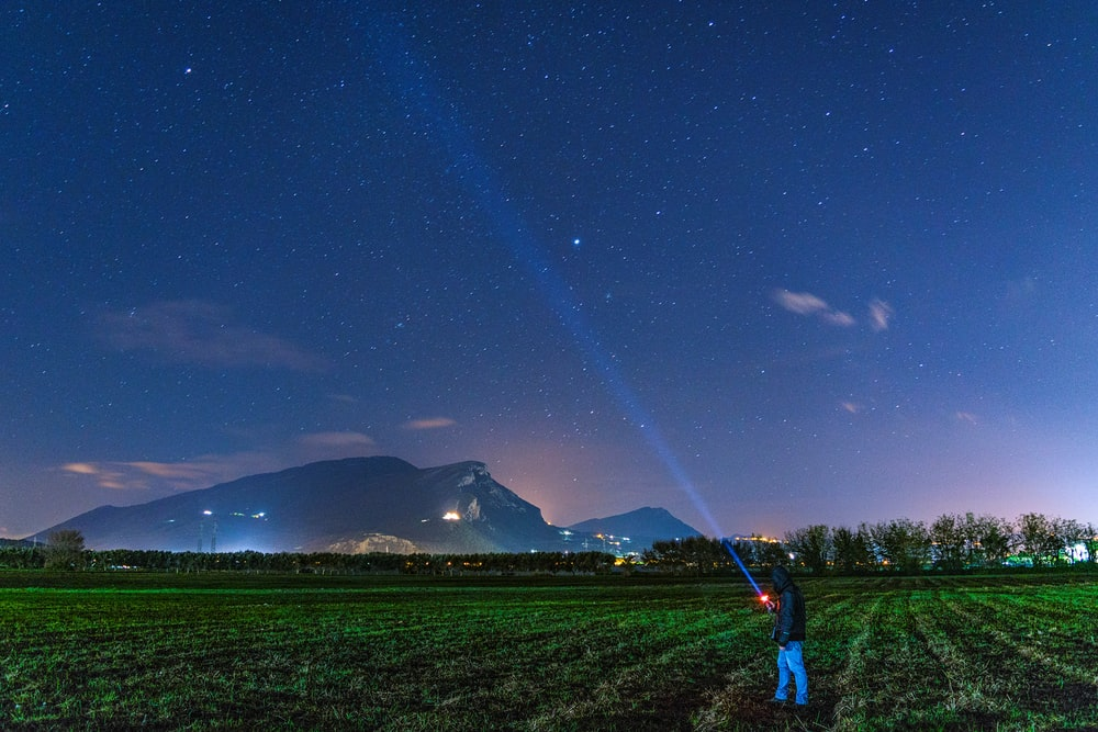 man standing on grass field while looking at the sky