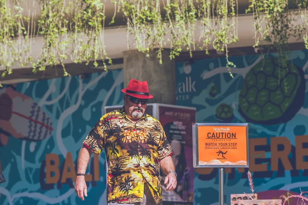 man standing near caution signage