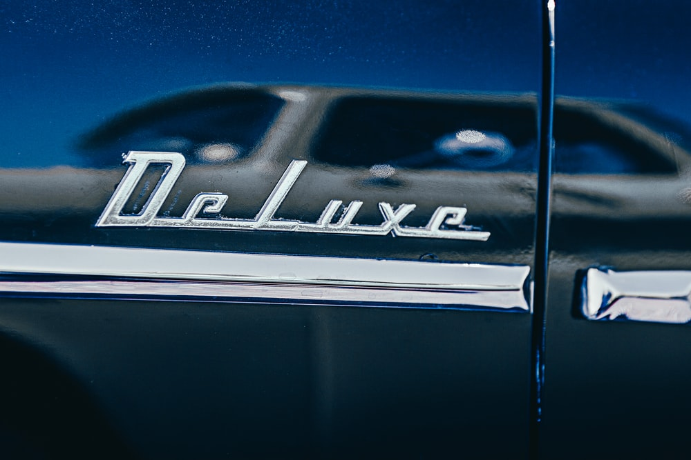 selective focus photography of chromed deluxe car emblem