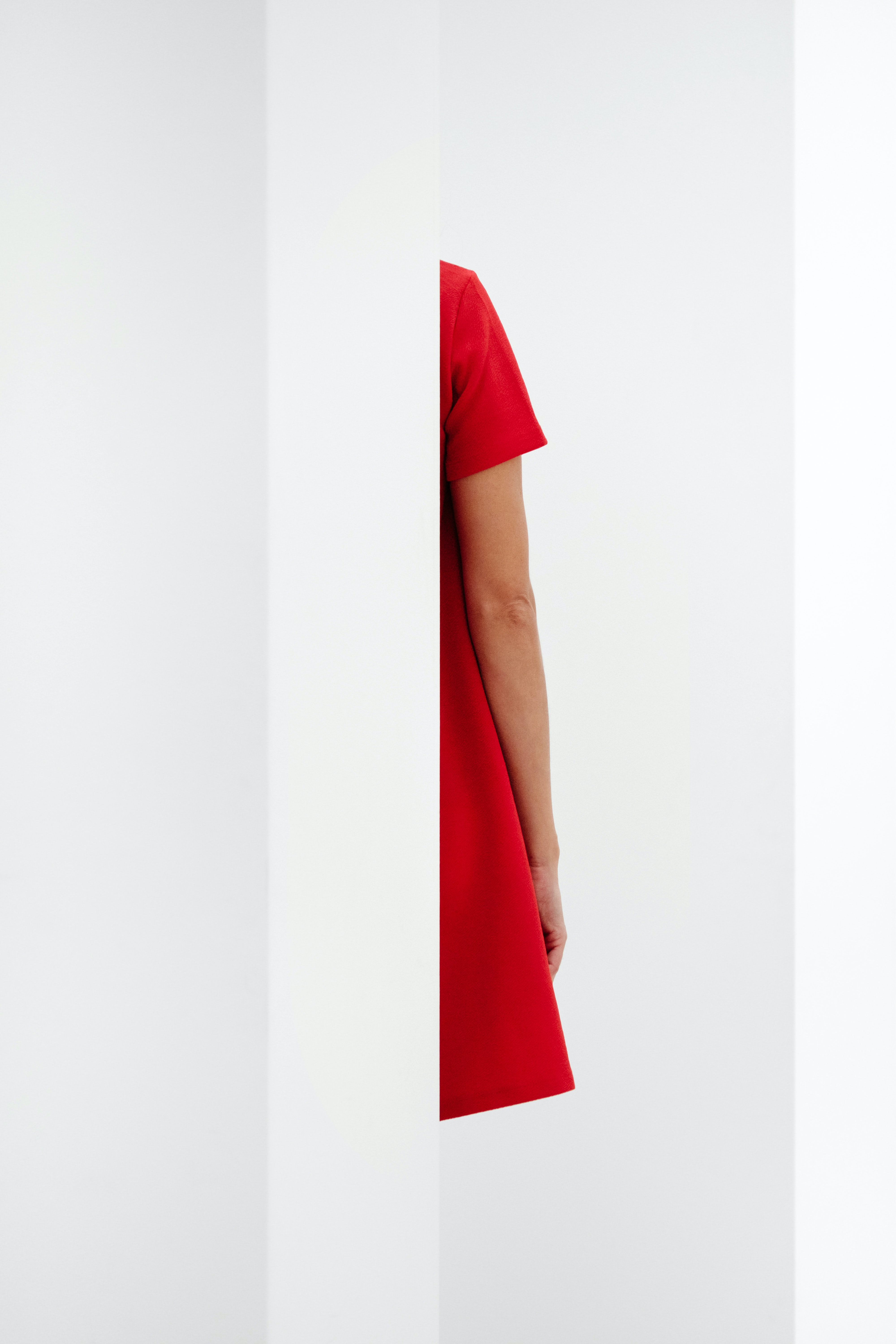 person in red top standing behind wall
