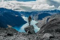 man standing on gray mountain near lake