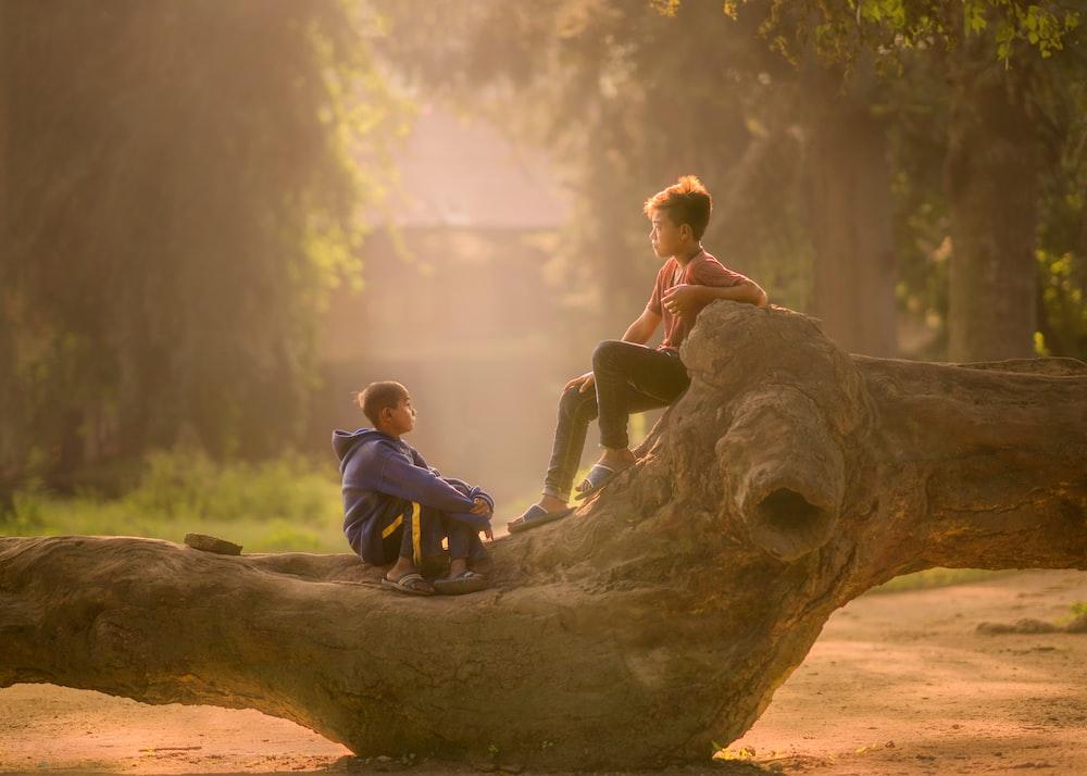two boy's sitting on log