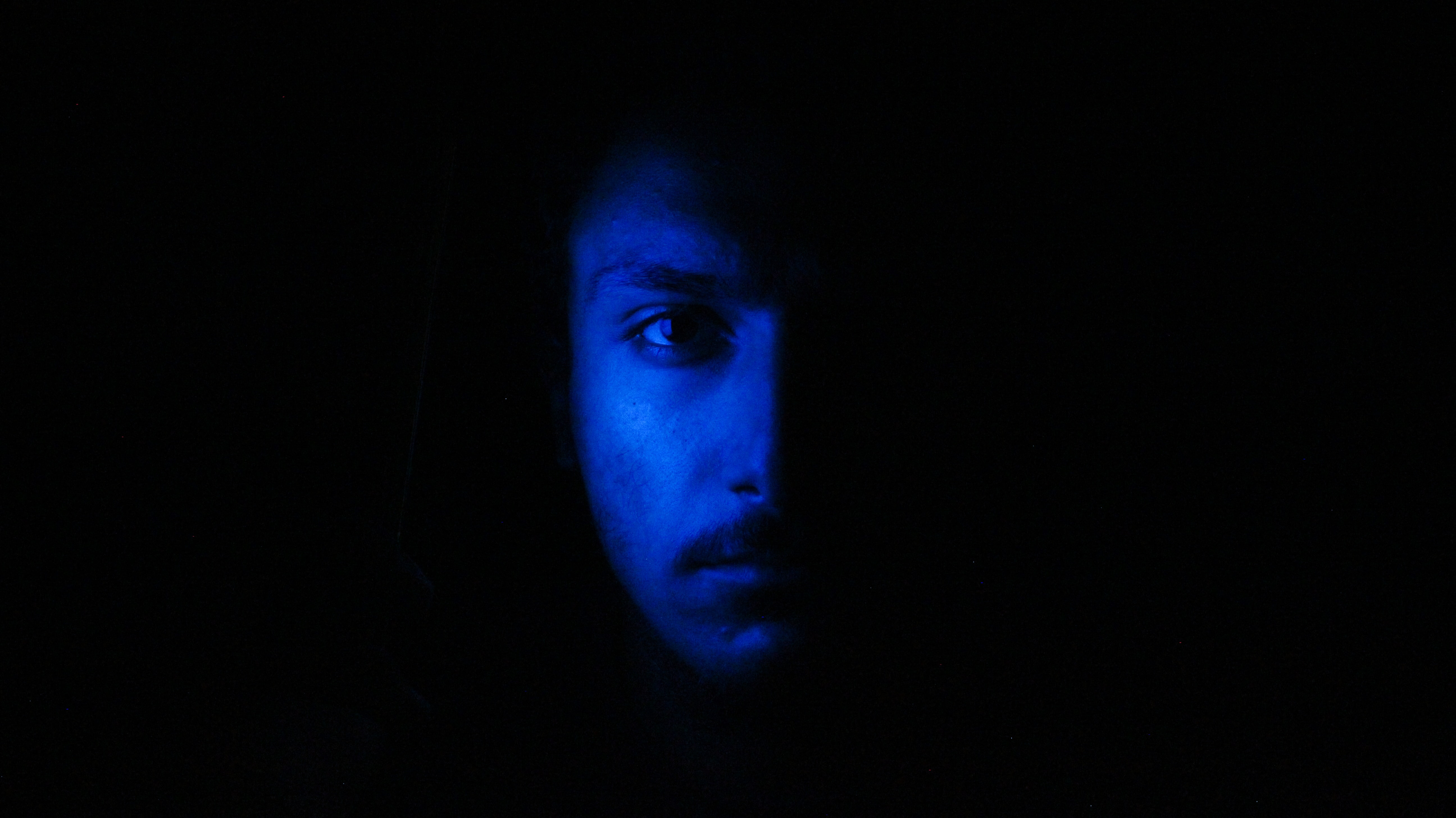 man's face against blue light
