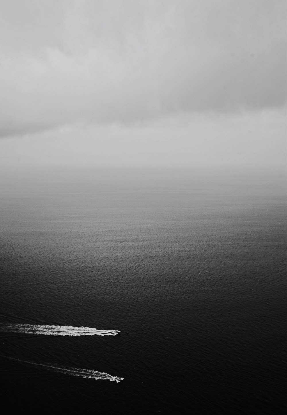 grayscale photography of two boats on a body of water