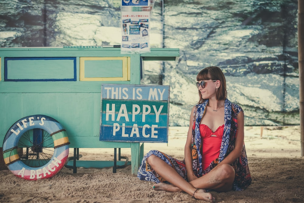 woman sitting on sand beside of This is My Happy Place signage