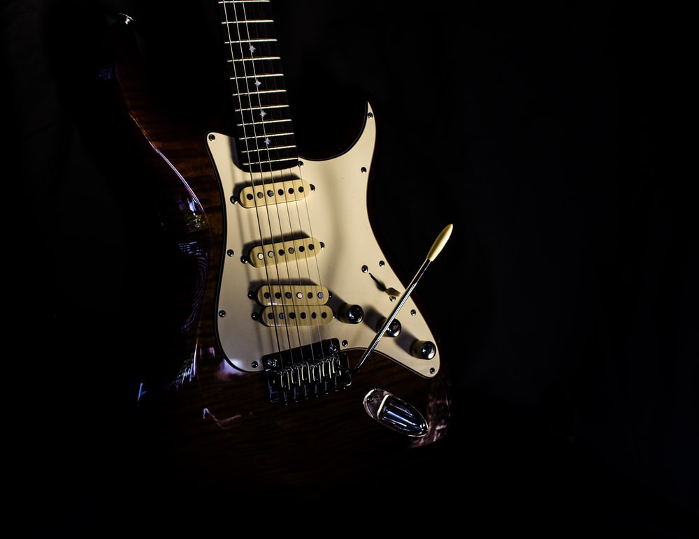 selective focus photography of white and red electric guitar